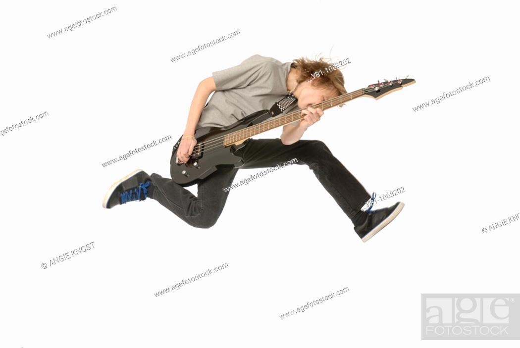 Stock Photo: Teenage boy playing bass guitar while jumping in the air.