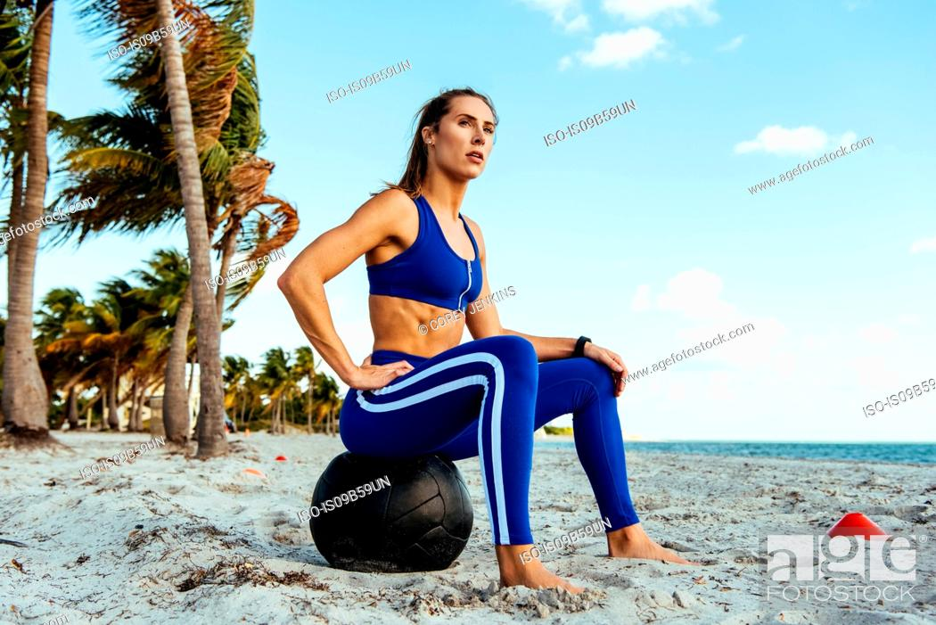 Stock Photo: Young woman training, sitting on exercise ball taking a break at beach.