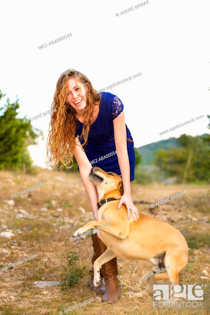 Stock Photo: USA, Texas, Young woman standing with Blackmouth Cur, smiling.