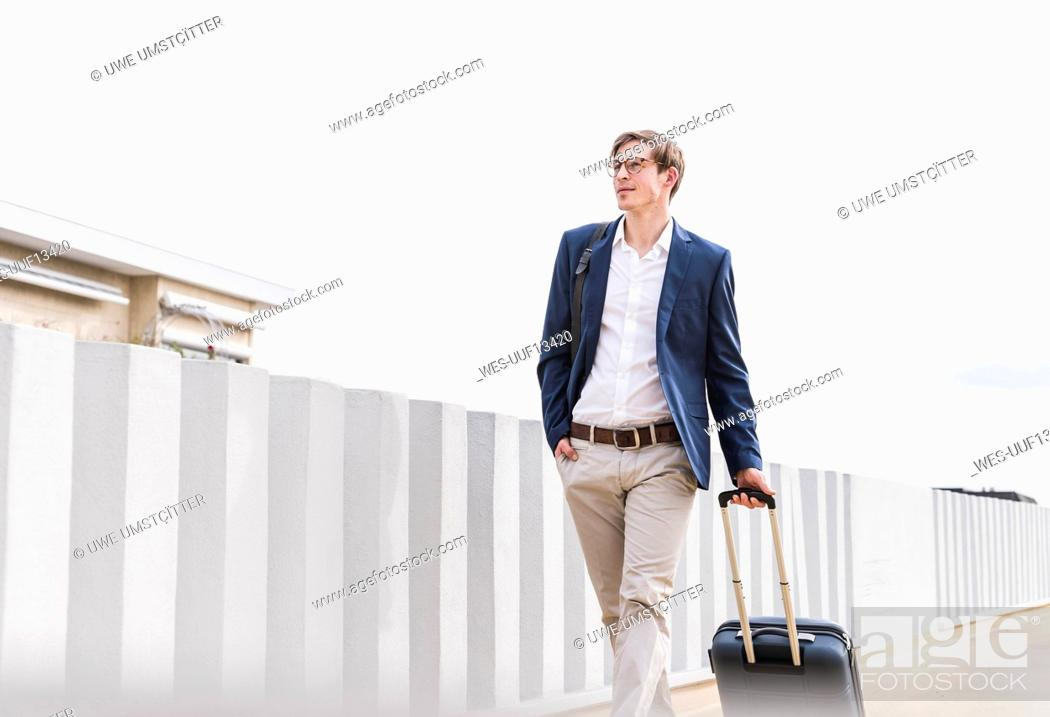 Stock Photo: Confident businessman with rolling suitcase walking at parking garage.
