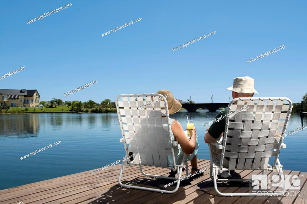 Stock Photo: Rear view of a couple sitting on chairs at the boardwalk.
