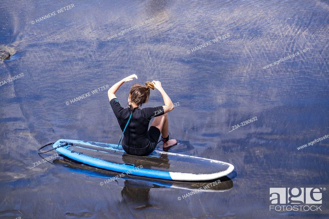 Stock Photo: Girl sitting on her surfboard tying her hair, Las Palmas de Gran Canaria, Canary Islands.
