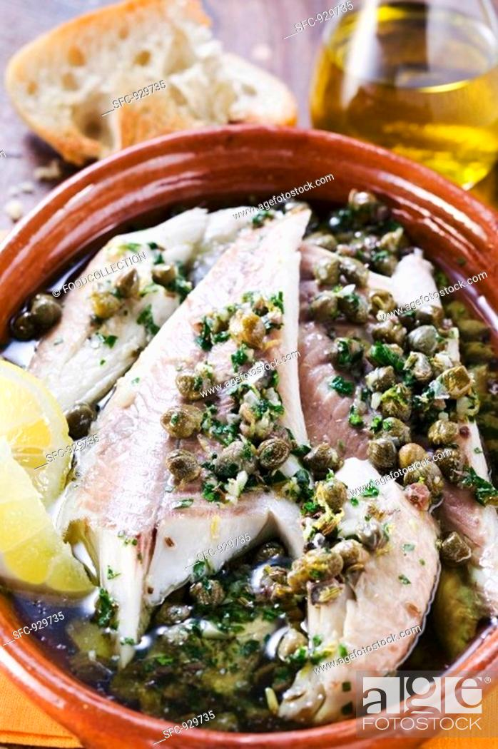 Stock Photo: Fish fillets in olive oil with capers.