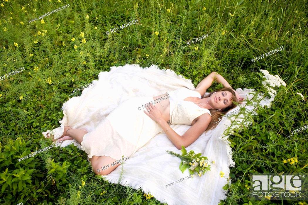 Stock Photo: Woman in white dress lying down in meadow with wildflowers.