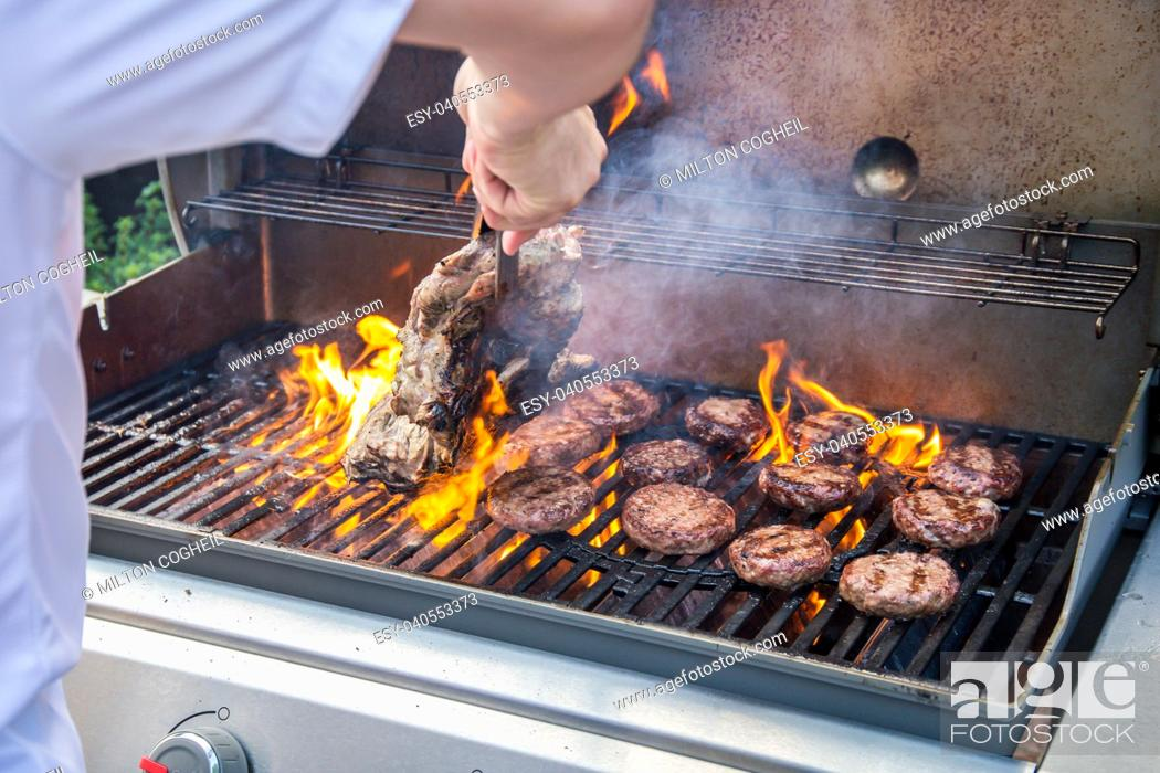 Stock Photo: Marinated lamb joint and beef burgers cooking on a barbecue.