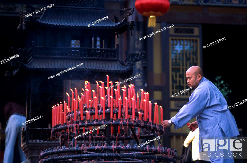 Stock Photo: Side profile of a monk arranging candles, China.