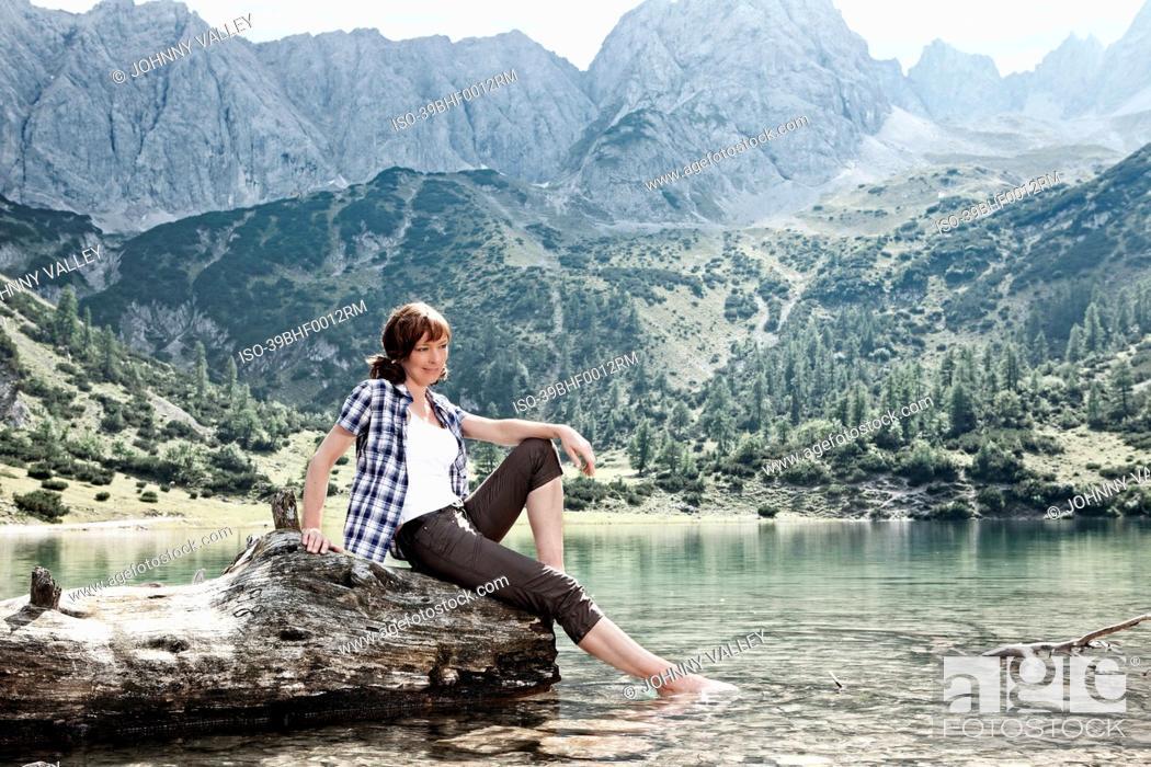 Imagen: Woman dangling feet in lake.