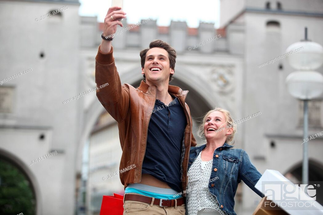 Stock Photo: Mid adult couple taking selfie in front of Neuhauser Tor, Munich, Bavaria, Germany, Europe.