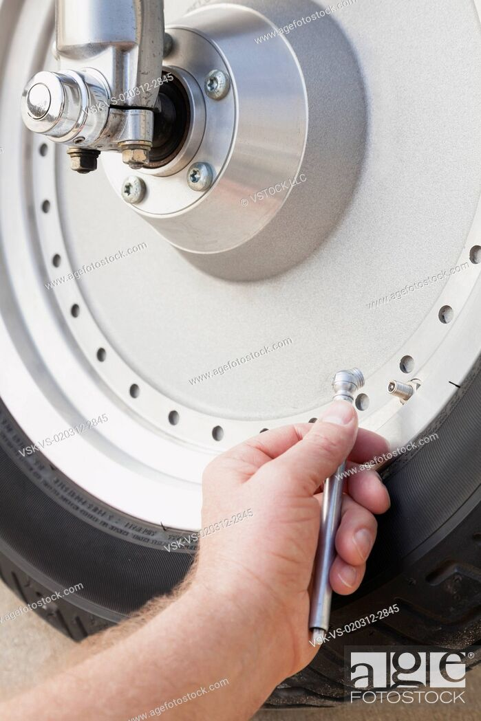 Imagen: USA, Illinois, Metamora, Close up of man's hand checking pressure in motorcycle tire.