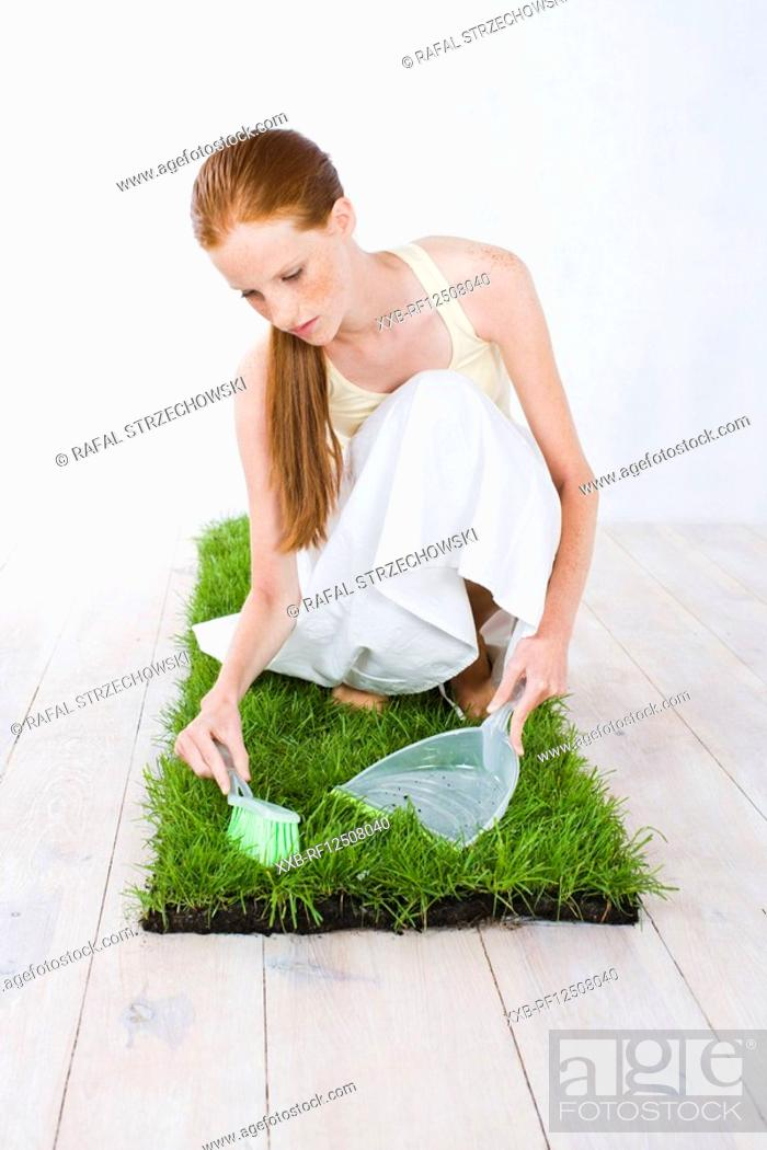 Stock Photo: young woman celaning grass.