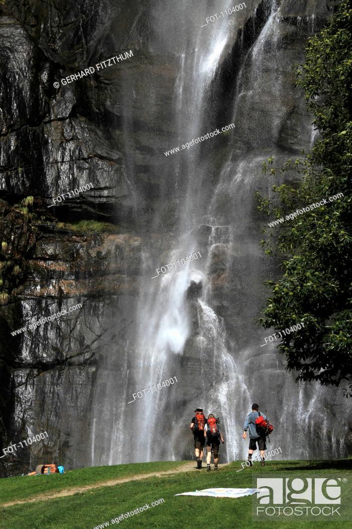 Stock Photo: Hikers walking towards a waterfall, Chiavenna, Lombardy, Italy.