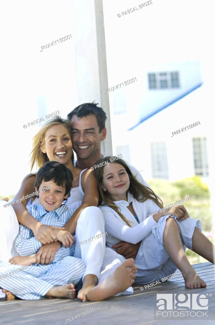 Stock Photo: Couple and two children smiling for the camera, sitting on wooden terrace.