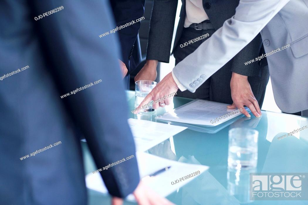 Stock Photo: Businesswoman pointing to paperwork on table in meeting.