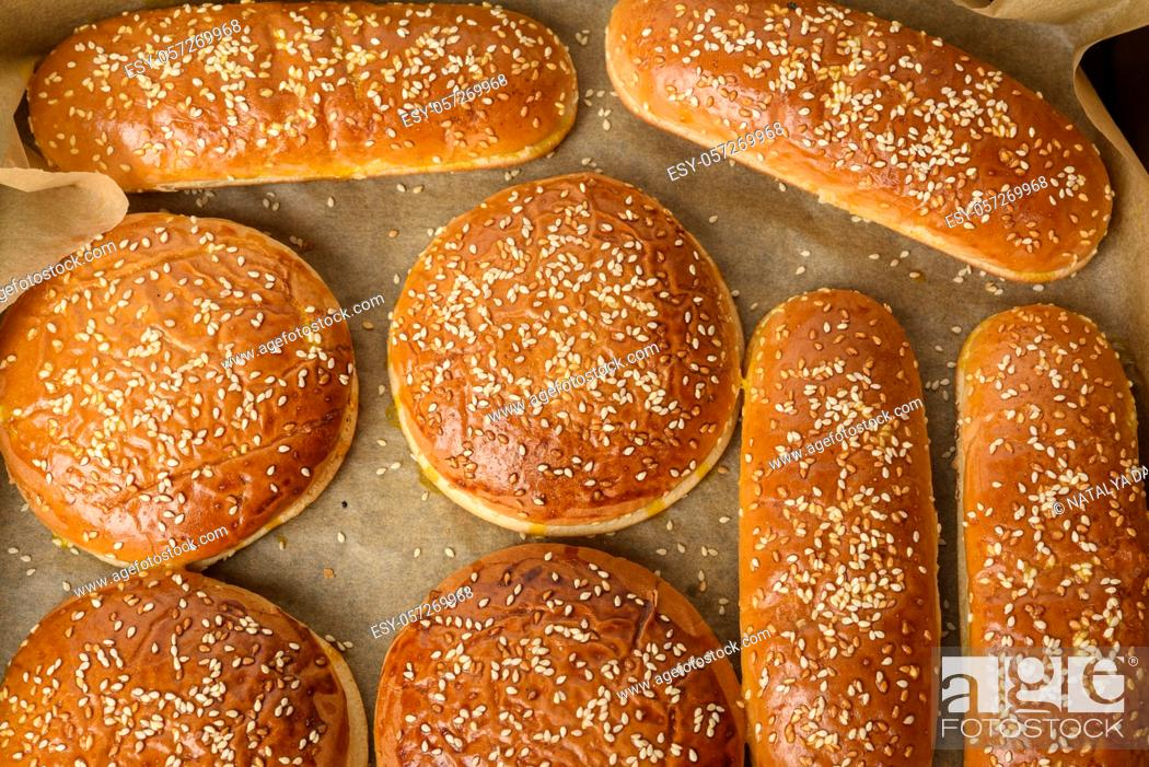 Stock Photo: baked sesame buns on brown parchment paper, ingredient for a hamburger, top view.