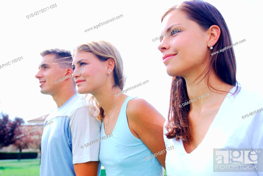Stock Photo: A young man standing with two young women.