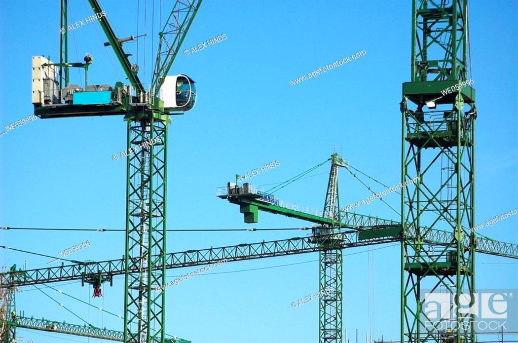 Stock Photo: Construction cranes on site at large scale urban regeneration project.