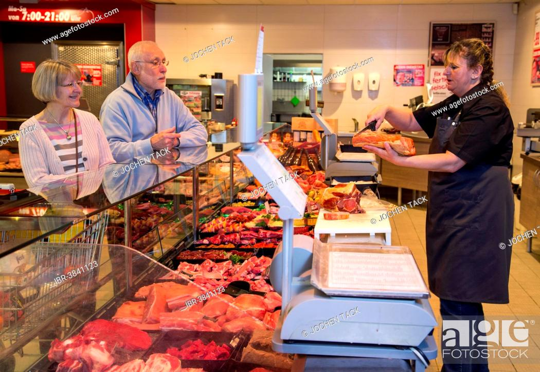 Stock Photo: Senior couple shopping at the meat counter in the supermarket, Germany.