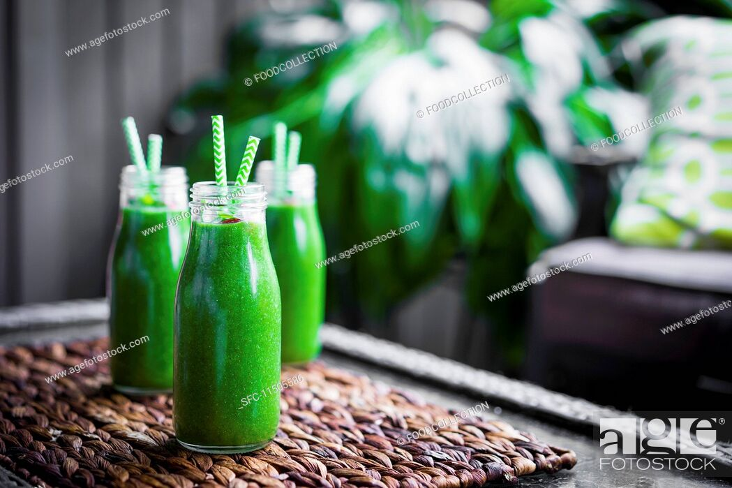 Stock Photo: Fresh green smoothie in glass bottles with straws.