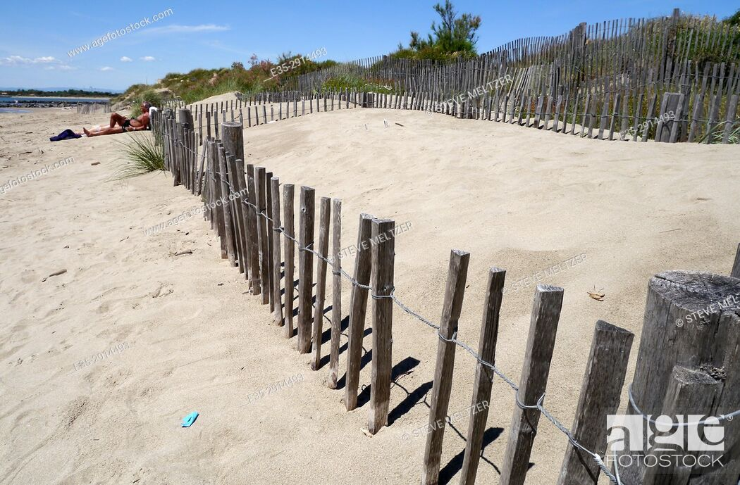 Stock Photo: A fence holds back the dunes at the beach at Grau d'Agde, Herault, France.