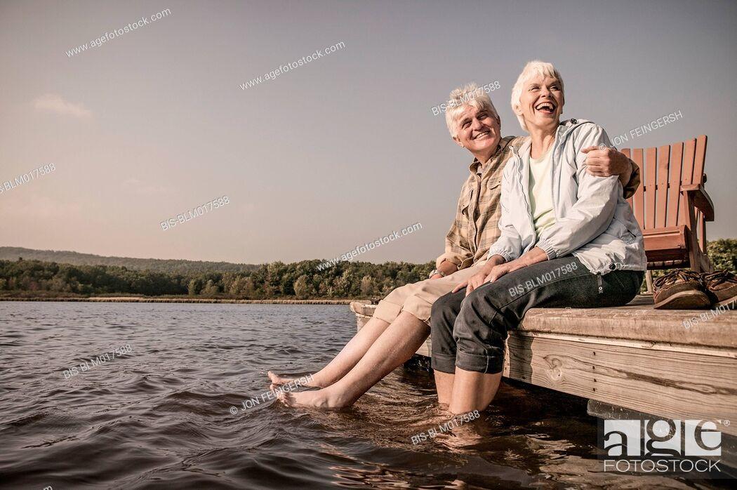 Imagen: Older Caucasian couple sitting on wooden dock.