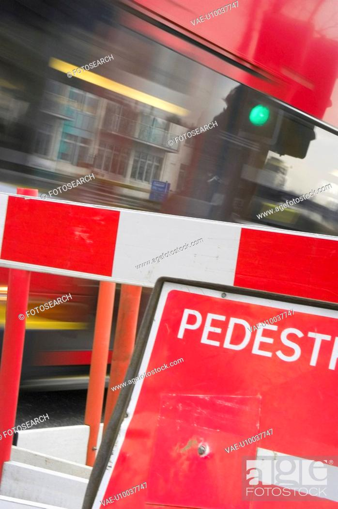 Stock Photo: A London bus rushing past a roadside construction barrier.