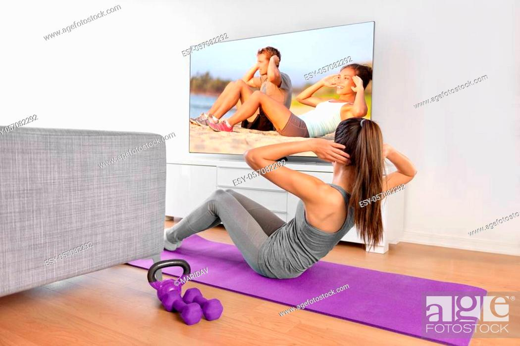 Stock Photo: Home workout - woman exercising in front of a flat screen watching a fitness program or exercising during a TV show lying on a yoga mat in front of the sofa in.