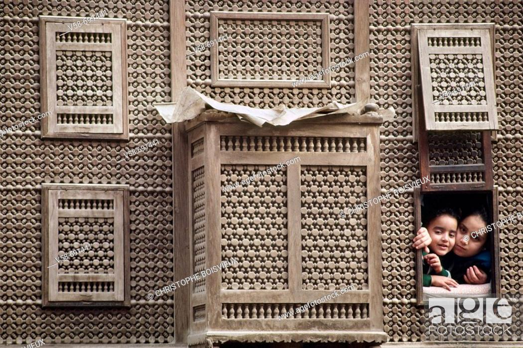 Stock Photo: Children watching the street life from a 'mashrabiya' window in Old Cairo. Egypt.