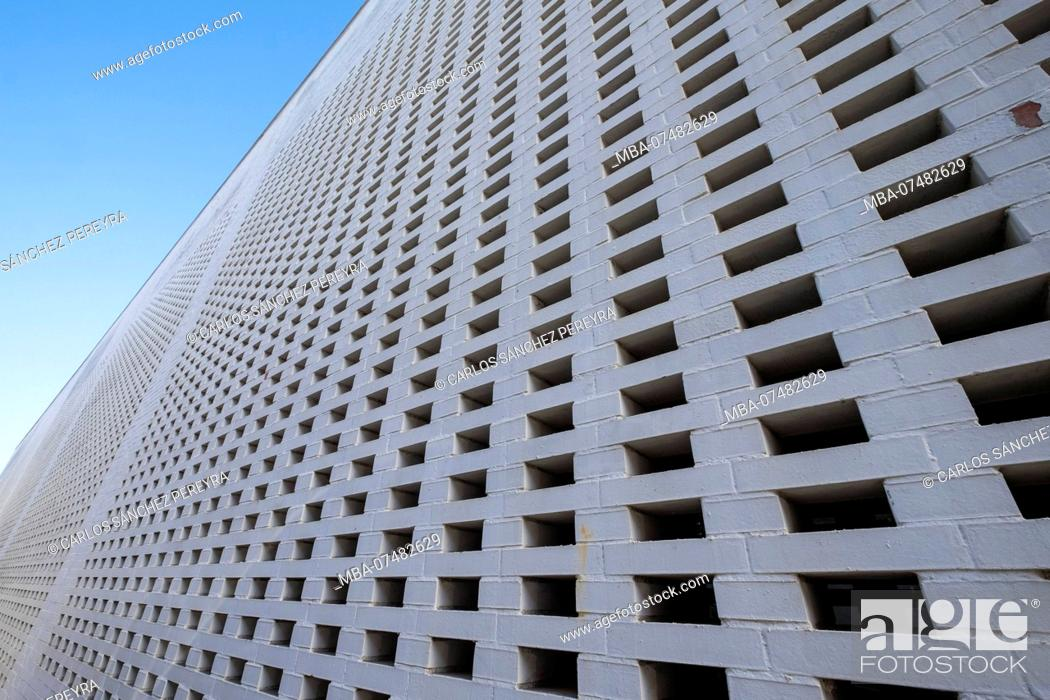 Stock Photo: white wall with a series of holes creating an abstract image.