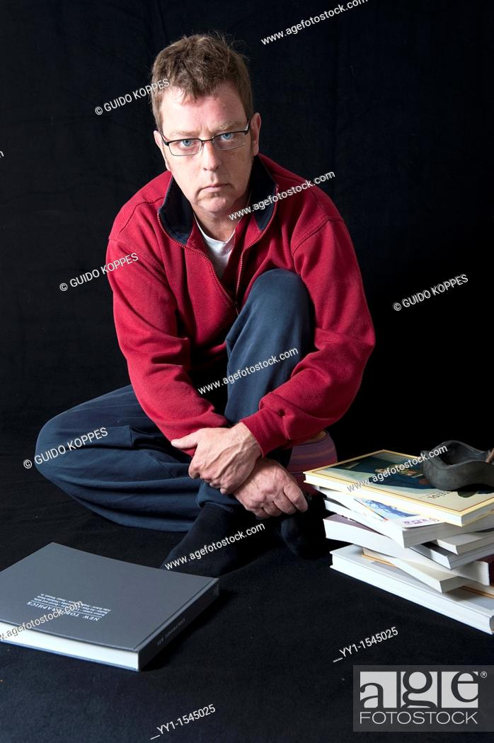 Stock Photo: Tilburg, Netherlands. Self-portrait of a male photographer, with photo-books in his studio.