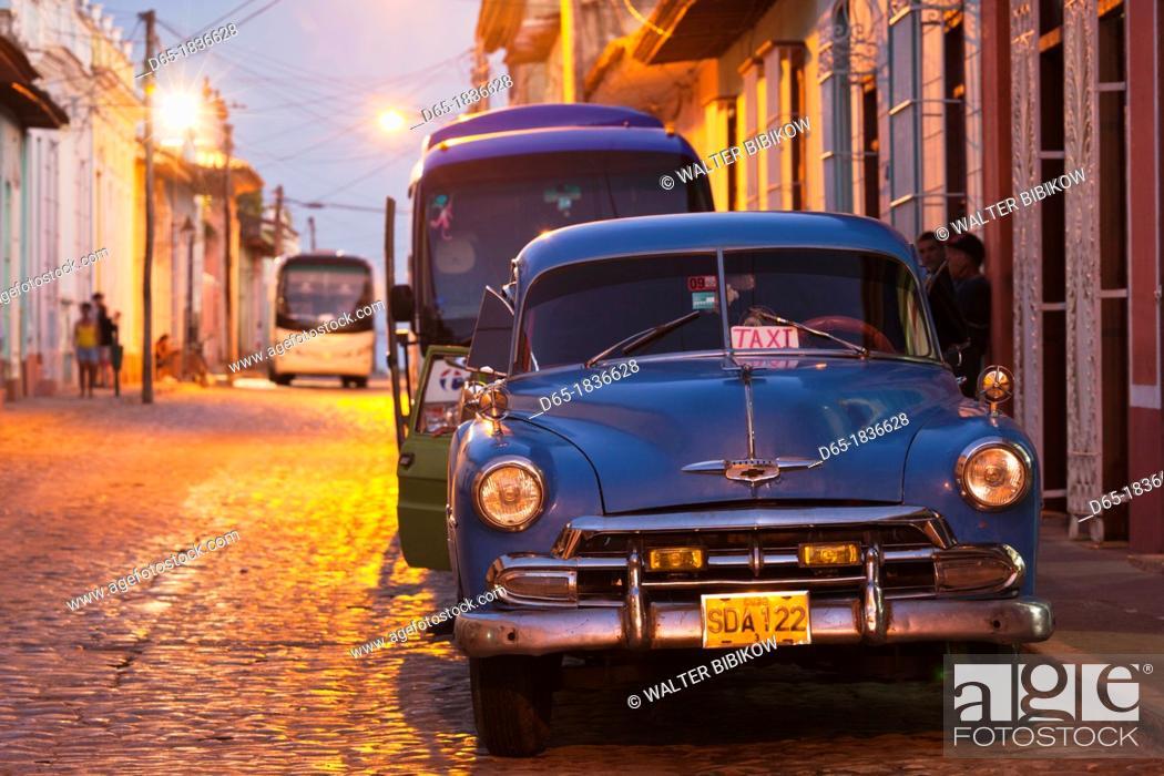Stock Photo: Cuba, Sancti Spiritus Province, Trinidad, taxis on Calle Antonio Maceo, dusk.