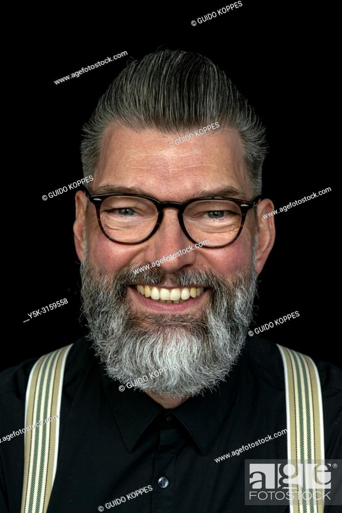 Stock Photo: Tilburg, Netherlands. Studio portrait of a mid adult, caucasian, male hipster with moustache and beard.