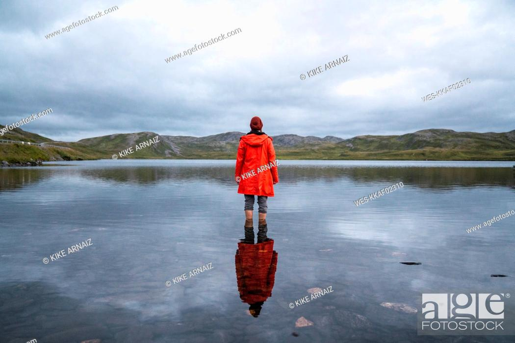 Stock Photo: Young man standing ankle deep in water, looking at distance, rear view.