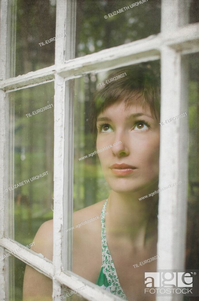 Stock Photo: young female looking up from behind a window.