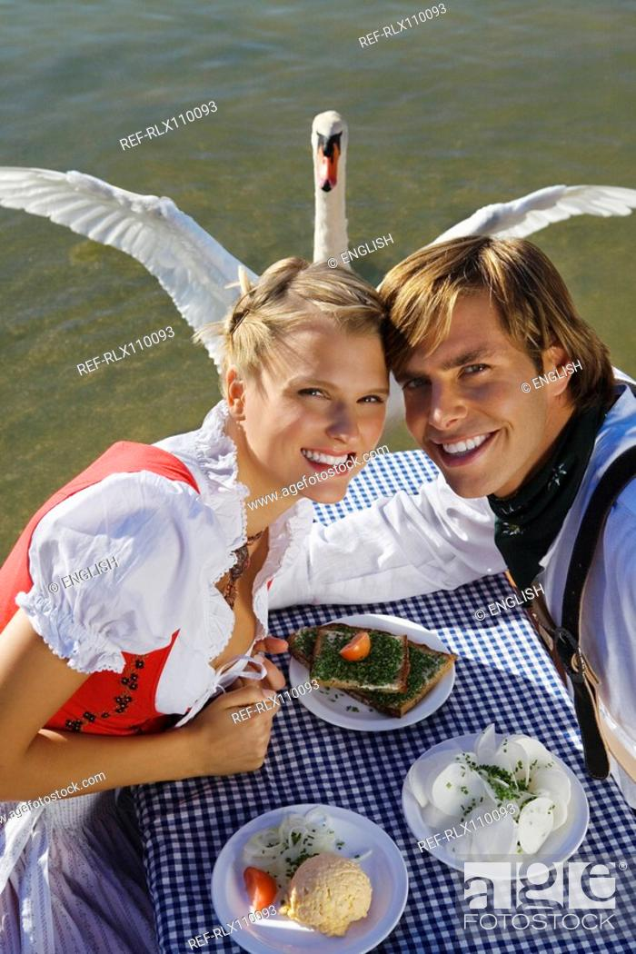 Stock Photo: Young couple in traditional Bavarian outfit, with swan in background, Munich.