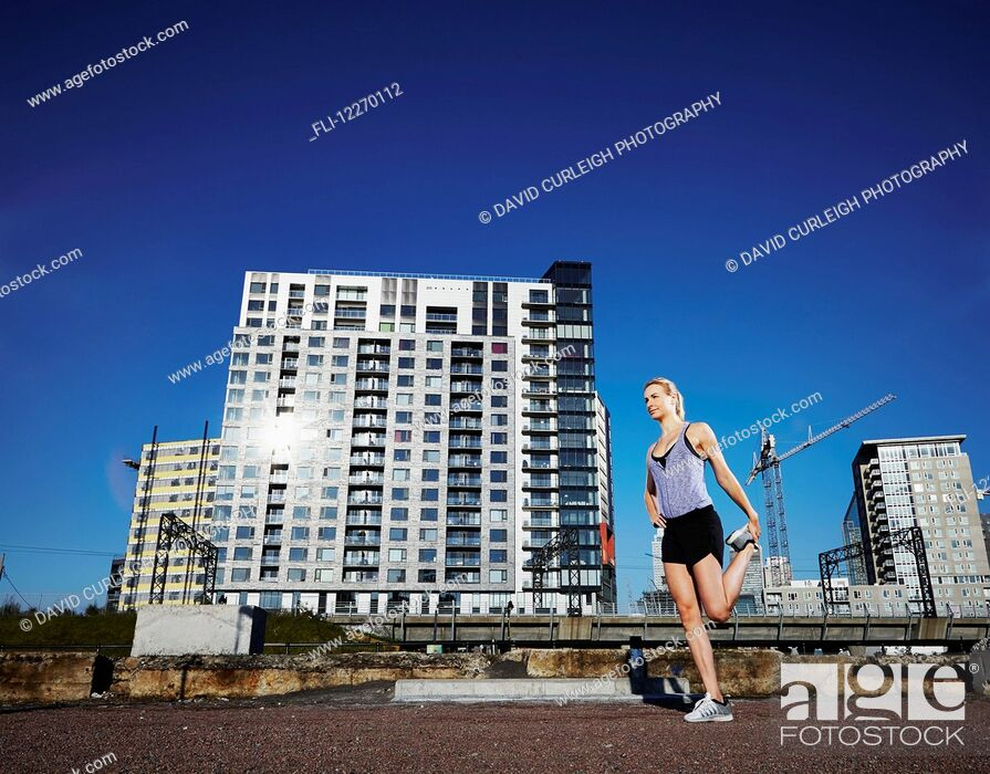 Stock Photo: Female runner stretching before a run in an urban environment; Montreal, Quebec, Canada.