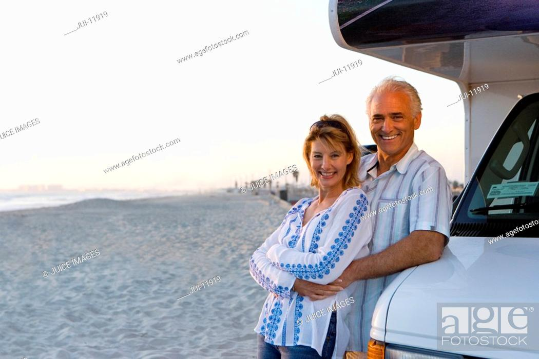 Stock Photo: Mature man embracing woman by motor home on beach, smiling, portrait.