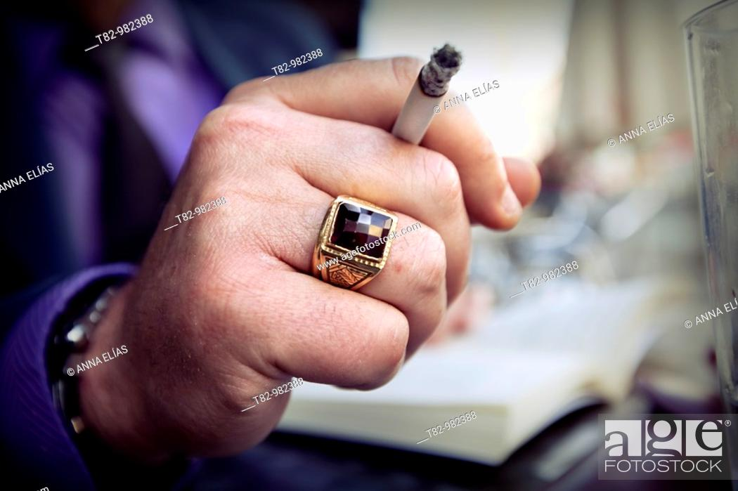 Stock Photo: primer plano de mano de hombre con anillo de oro y cigarrillo encendido,forefront of human hand with a gold ring and lit cigarette.