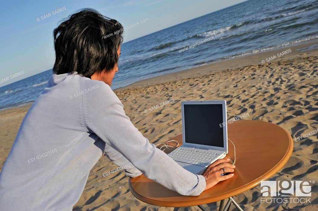 Stock Photo: Wman (43) on laptop by beach, Provence, France.