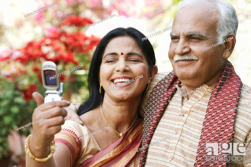 Stock Photo: Close-up of a mature couple looking at a mobile phone.