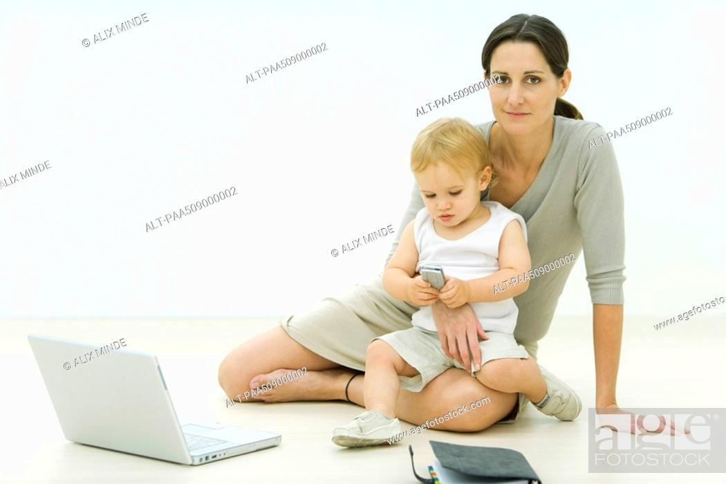 Stock Photo: Professional woman sitting on the ground with laptop, holding toddler on lap, toddler looking at cell phone.