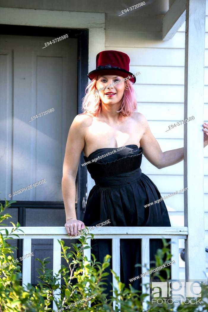 Imagen: A beautiful 34 year old blond woman wearing a red hat and a black dress standing on a porch of an old house.