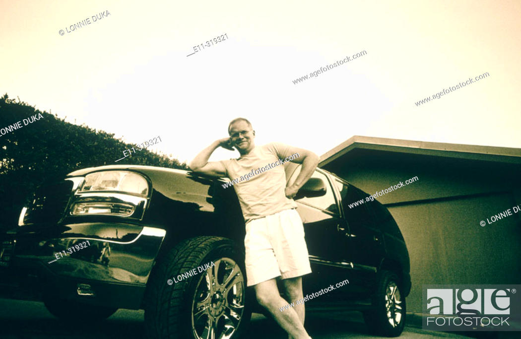 Stock Photo: Man posing in front of new SUV.