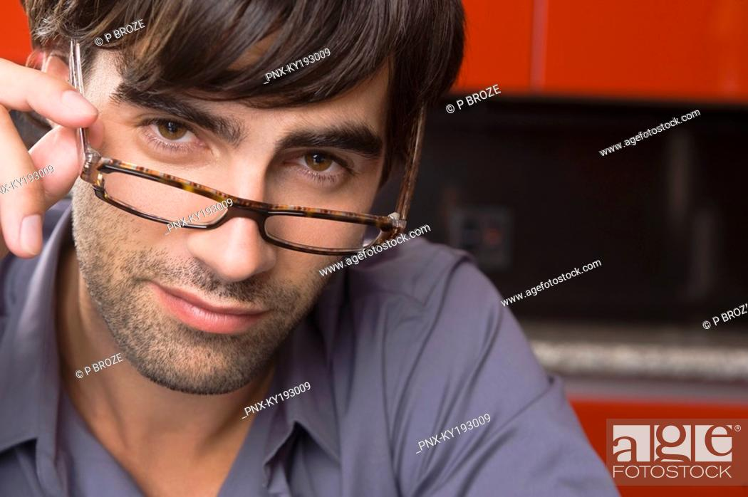 Stock Photo: Portrait of a man adjusting eyeglasses.