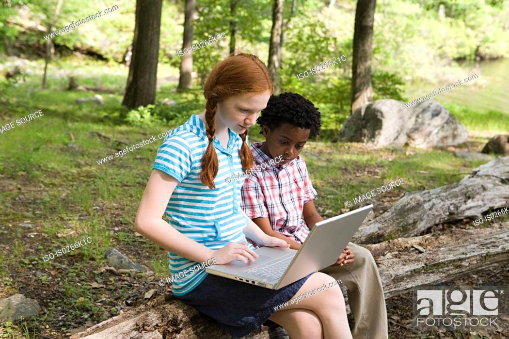 Stock Photo: Friends using a laptop in a forest.