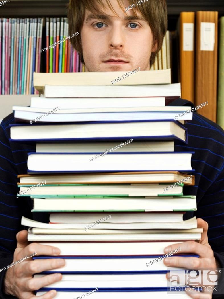 Stock Photo: Young man holding pile of books.