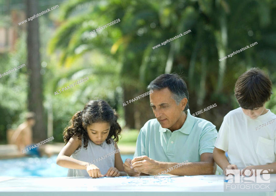 Stock Photo: Mature man putting together puzzle with grandchildren.