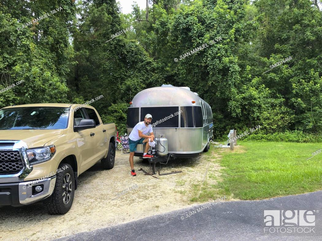 Stock Photo: Man standing by pickup truck and trailer in camping park, Ocala Florida, USA.