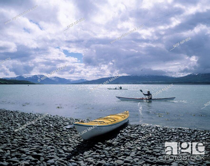 Stock Photo: Kayakers rowing along the coastline.