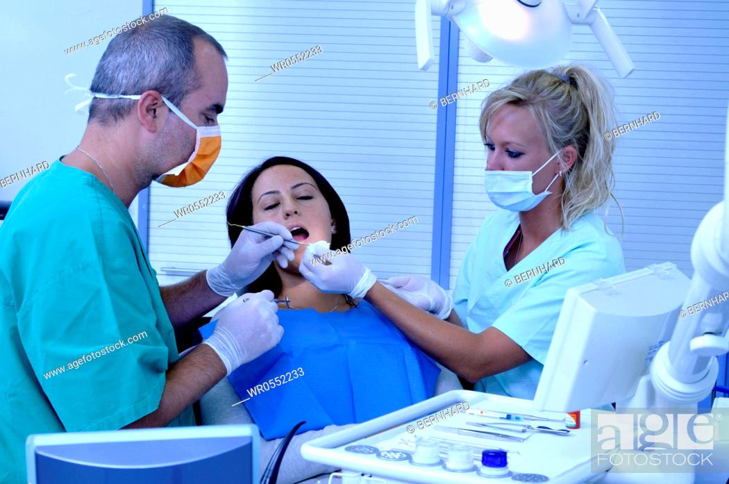 Imagen: female patient at the dentist sitting at the surgery couch - dentist's assistant in the back.