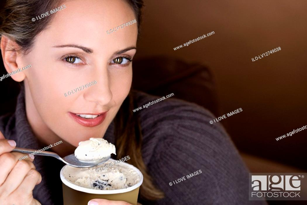 Stock Photo: A mid adult woman eating ice cream.